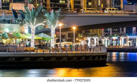 Promenade and bridge with traffic over canal in Dubai Marina timelapse at night, UAE. View from embankment  with palms, boats and towers. Dubai Marina is a district in Dubai with artificial canal cit
