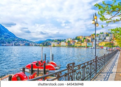 Promenade of luxury resort in Lugano with the beautiful scenery of Lake Lugano, surrounded by Alps mountains, the canton of Ticino, Switzerland.