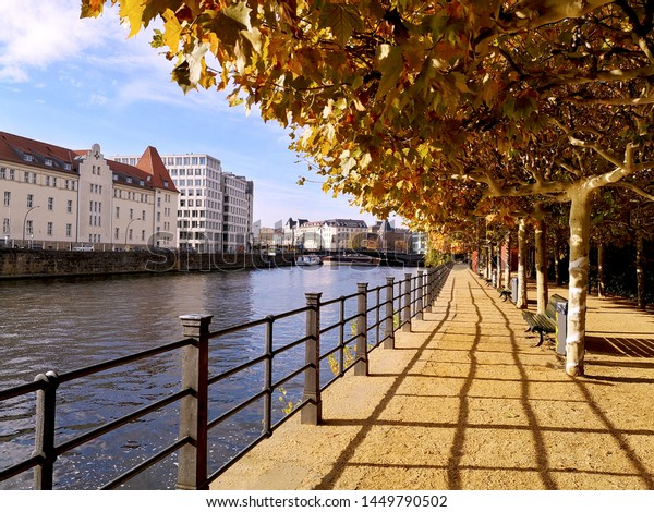 Promenade with metal guardrails, wooden benches and arcade of trees with autumn vibrant yellow and orange leaves next to calm water of Landwehr canal near Alexanderplatz on autumn tranquil sunny day,