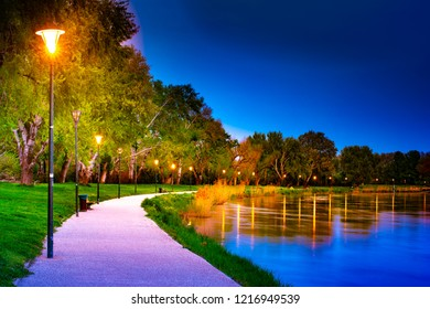 Promenade on the shore of river Rhone in Avignon at night with beautiful lantern lights and trees.