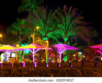 Promenade at the Playa de las Americas on tenerife at night. The palm trees are illuminated from below in bright green, the parasols in front in violent purple.