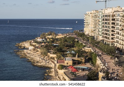 Promenade at Sliema on Malta in late Autumn with motor boat skimming across the sea and promenade with tourists in the foreground.