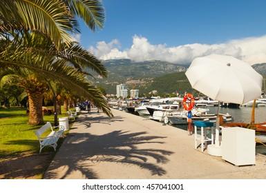 Promenade of Slovenska Obala with boats and palm trees in Budva