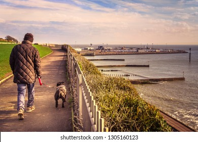 The promenade at Westcliff, Ramsgate in Kent, UK on the Royal Esplanade. A man walks his dog as the car ferry leaves the harbour after delivering cars to the port.