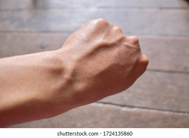 Prominent dorsal metacarpal veins in left hand of Southeast Asian, Chinese young man. Isolated on wooden background.