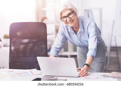 Prominent mature business lady using her laptop