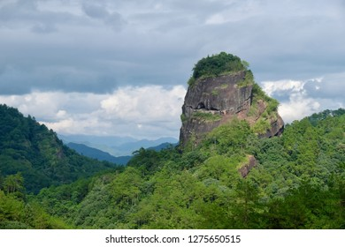 prominent spiral brown stone rock hill with green trees covered. Wide fresh wild lush green forest. blue mountains and sea of clouds. sunny sky shadows. Mount Wuyi in Fujian China