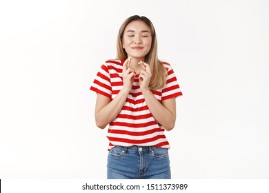 Promise behave well just fulfill my dreams. Dreamy cute optimistic asian blond girl 20s close eyes smiling delighted make wish cross fingers good luck anticipating only positive news
