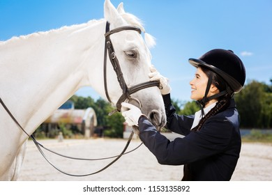 Promising horsewoman. Young promising horsewoman feeling excited while coming to her lovely white horse