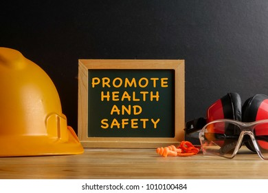 PROMOTE HEALTH AND SAFETY CONCEPT. Personal protective equipment on wooden table over white background.