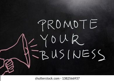 Promote your business concept words written on blackboard