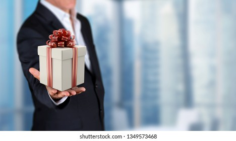 Promotion consept in business, businessman showing 3D render gift box on his hand in a office. Skycrapers are in background.