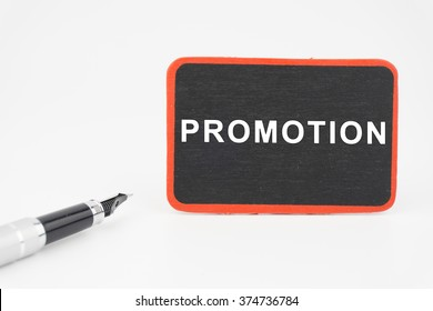 PROMOTION word on mini blackboard  with pen over white background