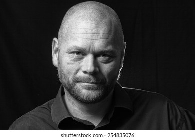 A promotional actor head shot, low key.  Actor looking directly to camera.