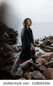 promotional photography of a girl in a dress of high boots and a coat near the water in rainy weather