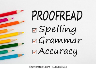 PROOFREAD written on a white background and colour pencils.