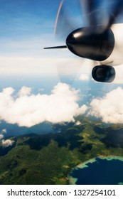 Propeller aircraft wing over tropical islands. Aerial view of airplane flying above shade clouds and sky