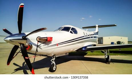 Propeller airplane parked outside hanger