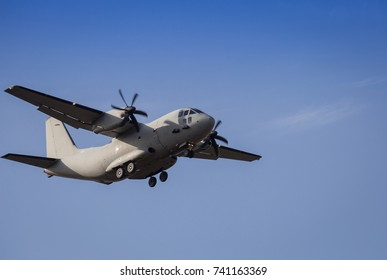 Propeller plane lit by the sun  against a blue sky with white clouds - in motion and close-up
