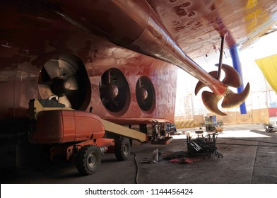 Propeller under reconstruction. Under the ship. Big ship under repairing on dry dock in shipyard