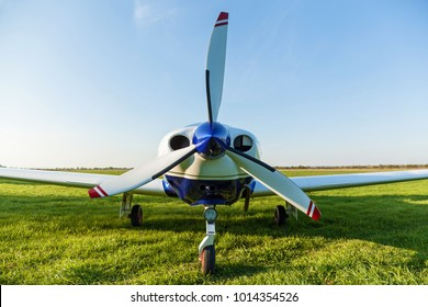 The propeller of a white airplane on the grass close up. Airplane propeller.