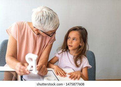 Proper articulation therapy for girl. Stuttering girl and speech therapist. Senior female speech therapist helping a young patient. Repeat after me.. Session with alphabet learning