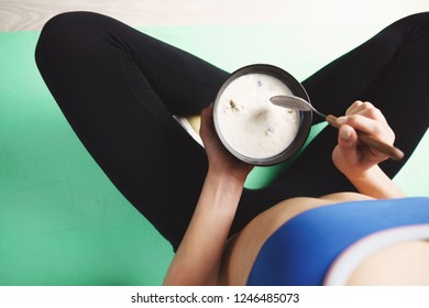 proper nutrition, diet, healthy lifestyle and sport. Young fit woman having light snack after workout. eating protein smoothie bowl