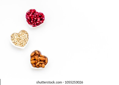 Proper nutrition for pathients with heart disease. Cholesterol reduce diet. Oatmeal, pomegranate, almond in heart shaped bowl on white background top view copy space