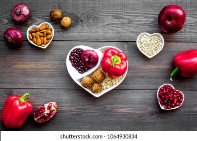 Proper nutrition for pathients with heart disease. Cholesterol reduce diet. Vegetables, fruits, nuts in heart shaped bowl on dark wooden background top view