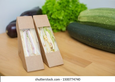 Proper nutrition a sandwich lies on a wooden table in the kitchen on green vegetables background. Fitness Fast Healthy Nutrition Concept