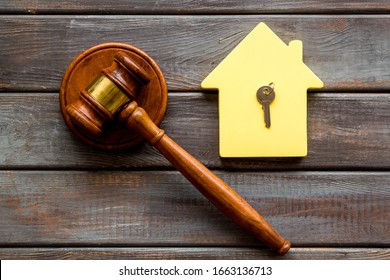 Property auction concept. Judge gavel near house on dark wooden background top-down