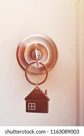 Property Concept, Home key with metal house keychain in keyhole.