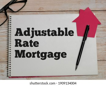 Property concept. Top view text Adjustable Rate Mortgage written on notebook with pen,house cupboard and eye glasses on wooden table.
