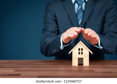 Property (family house) insurance protection concept. Insurance agent with wooden model of the house and protective gesture.