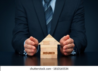Property (family house) insurance protection concept. Insurance agent protect by hand model of the house with text insured, made from wooden pieces.