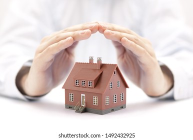 Property insurance concept. Small toy house covered by hands