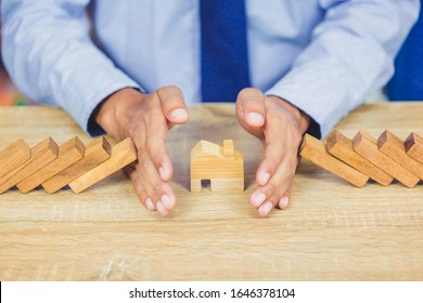 Property insurance. and security concept, businessman hand stopping risk the wooden blocks from falling on house.