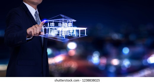 Property insurance and security concept. Real estate agent business touching symbol of house on city night background.
