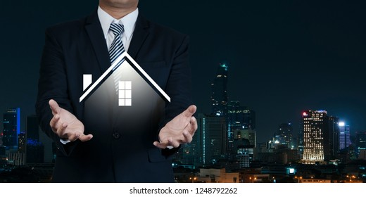 Property insurance and security concept. Real estate agent business hold symbol of house on city night background.