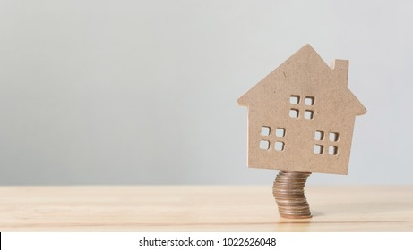 Property investment and house mortgage financial. Risk management concept. Wooden home on coins stack