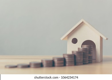 Property investment and house mortgage financial concept, Money coin stack with wooden house