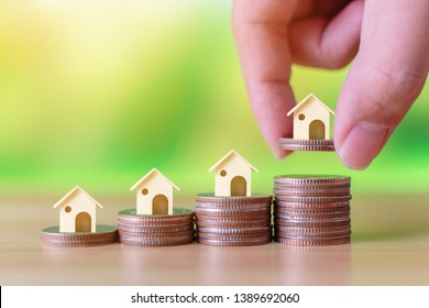 Property investment and house mortgage financial concept. Hand putting money coin stack step up growing growth house