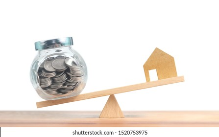 Property investment and house mortgage financial concept,Model house and money coins balancing on seesaw