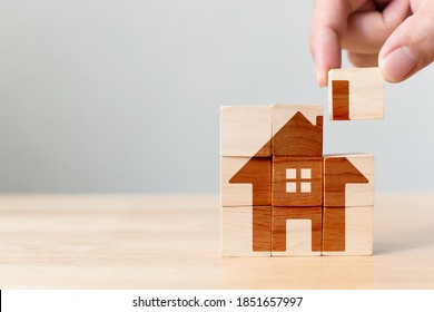 Property investment and house mortgage financial real estate concept. Wooden cube block puzzle with home image