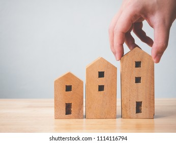 Property investment real estate and house mortgage financial concept. Hand holding wooden home on table