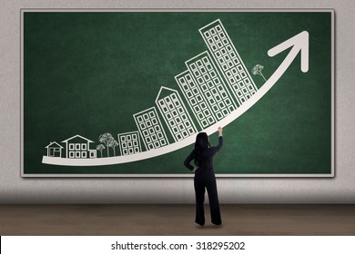 Property investor draws increasing business property chart with arrow and house picture on the blackboard