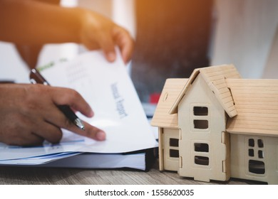 Property mortgage real estate house concept. Businessman hands signing documents file paperwork financial in investment business on desk office with chart report document contact customer. Home focus