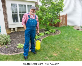 Property owner or gardener with a portable sprayer filled with weed killer to eradicate garden weeds standing in front of his house