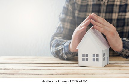Property Protection Concept! Home insurance. Covered in hands.