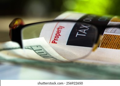 Property taxation news with dollar bill through glasses.